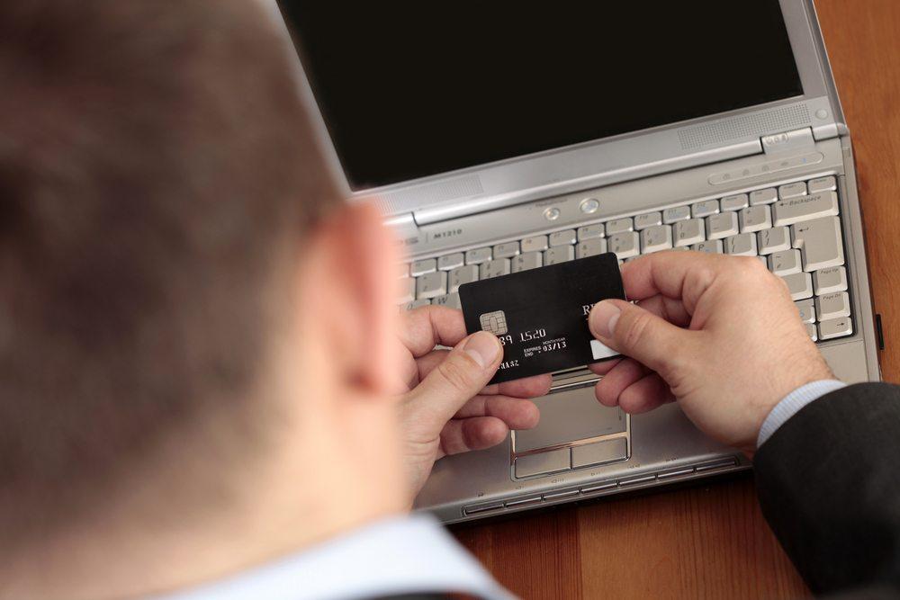 homme qui tient une carte bancaire devant son ordinateteur